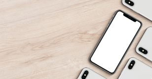 Smartphonesmodellbaner med den lekmanna- bästa sikten för copyspacelägenhet som ligger på träkontorsskrivbordet royaltyfria foton