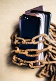 Smartphons in chains. Old rusty chains. Black smartphone