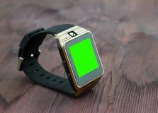Smartwatch изолировало на деревянной предпосылке с экраном зеленого цвета ключа chroma Стоковое Изображение