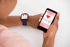 Рука с чернью и Smartwatch показывая тариф биения сердца Стоковое фото RF