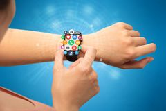 Smartwatch with application icons. Hand with smartwatch and application symbols nearby Royalty Free Stock Photos