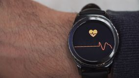 Smartwatch che mostra la frequenza cardiaca all'utente L'orologio è sulla sua mano destra archivi video