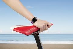 Smartwatch d'uso del sedile della bici della tenuta della mano della donna del primo piano Fotografie Stock Libere da Diritti