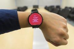 Smartwatch de regard d'homme d'affaires au programme d'ordre du jour d'exposition de lieu de réunion quand où et organisateur Image stock