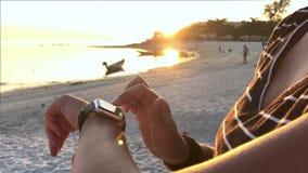 SmartWatch Giovane donna che per mezzo dell'orologio astuto sulla spiaggia stock footage
