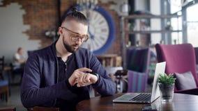 Smartwatch op a bemant hand Hipster zit in een koffie en gebruikt zijn slim horloge, kan hij de berichten bekijken, activeren stock video