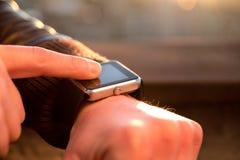 Smartwatch触摸屏幕在手边使用他的smartwatch app 库存图片
