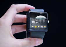 Smartwatch with weather icon in hand. Stock Photo