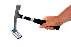 Smash the cell phone. Hammer comming down on to a cellphone to smash it to pieces royalty free stock photo