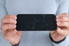 Smash shattered cracked screen phone repair. Smashed shattered cracked screen. man holding damaged smart phone. mobile devices repair service concept royalty free stock image