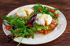 Smashed avocado and poached egg toast on green salad for breakfast Stock Photo