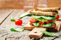 Smashed avocado spinach tomato grilled rye sandwich. Toning. selective focus Stock Photos