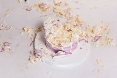 Smashed cake on white table for first birthday. Messy pieces.  Royalty Free Stock Image