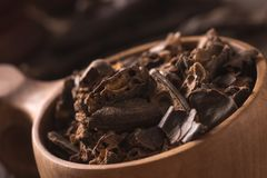Smashed carob pods. On a wood with cup Stock Photography