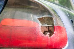 Smashed and damaged rear stop light on the blue car, damaged by vandals or in crash accident close up stock photography