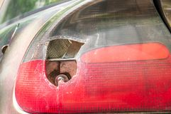 Smashed and damaged rear stop light on the car, broken by vandals or in crash accident close up.  Stock Photography