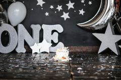 Smashed first birthday white cake with stars and one candle for little baby boy and decorations. Black background. Big silver stock photos