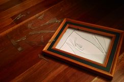Smashed Glass Wooden Picture Frame. Smashed glass picture gram on wooden floor with white blank picture space. Broken glass scattered on floor Stock Photos