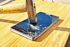 Smashed phone screen on a table with a hammer stock photography