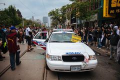 Smashed police car. TORONTO, CANDA - JUNE 26, 2010: Protestors and onlookers surround a police car on Queen St. West that was vandalized Royalty Free Stock Images