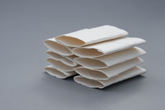 Smashed toilet rolls stack up on grey Stock Photography