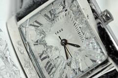 Smashed watchface. A closeup of an analog watchface, with the glass smashed and broken Royalty Free Stock Photos