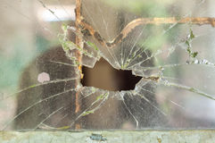 Smashed window pane with a hole in the middle Stock Image