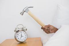 Smashing alarm clock with hammer Royalty Free Stock Photography