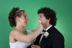 Smashing cake. A couple with their wedding cake stock photos