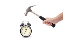 Smashing a clock. Hand hitting an alarm clock with a hammer Stock Photo