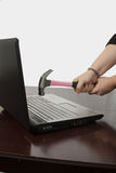 Smashing computer. Laptop computer on a brown desk and a pair of hands holding a pink hammer over keyboard royalty free stock image
