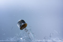 Smashing light bulb. A glass light bulb whcih is in the process of being smashed Stock Image