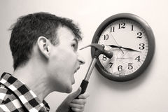 Smashing time. Tired, freaked-out man preparing to smash clock Royalty Free Stock Photography