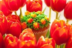 Smaskig muffin och röda tulpan på ljus bakgrund Selektiv focu Royaltyfri Foto