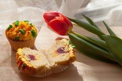 Smaskig muffin och röda tulpan på ljus bakgrund Selektiv focu Arkivfoto