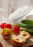 Smaskig muffin och röda tulpan på ljus bakgrund Selektiv focu Arkivbild
