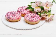 Smaskiga donuts med b?r p? den vita tr?bakgrunden S?t mat close upp arkivfoto