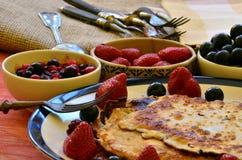 Smaskiga kräppar med jordgubbar och blåbär på träbakgrund Fotografering för Bildbyråer