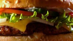Smaskigt snabbmatbegrepp Ny hemlagad grillad hamburgare med den köttlilla pastejen, tomater, gurkan, grönsallat, löken och sesam lager videofilmer
