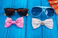Smazzi con il farfallino e gli occhiali da sole rossi su di legno blu Fotografie Stock