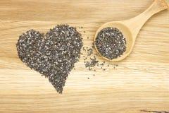 Símbolo del corazón hecho de las semillas y de la cuchara negras del chia Imágenes de archivo libres de regalías