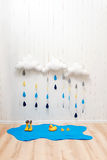 Símbolos de tempo A decoração feito a mão da sala nubla-se com gotas da chuva, poça, as botas de borracha da criança e os patos a Foto de Stock