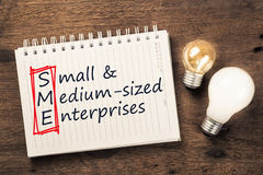 SME and Bulbs. SME or Small and Medium Sized Enterprises text on notebook with two different light bulbs Stock Images