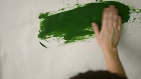 Smear green paint on a white background. Woman smears draws green paint on a white surface, smear green paint on a white background stock video