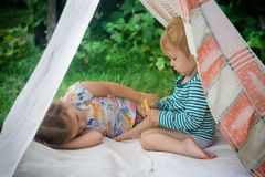 Smeared children play in nature in an improvised house. stock photo