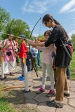 Children learn to shoot with a bow and arrow. Smederevo, Serbia - May 02, 2019: Medieval warriors Camp in Smederevo Fortress. Medieval archer with bow and arrow royalty free stock photography