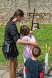 Children learn to shoot with a bow and arrow. Smederevo, Serbia - May 02, 2019: Medieval warriors Camp in Smederevo Fortress. Medieval archer with bow and arrow royalty free stock photo