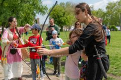 Children learn to shoot with a bow and arrow. Smederevo, Serbia - May 02, 2019: Medieval warriors Camp in Smederevo Fortress. Medieval archer with bow and arrow stock photo