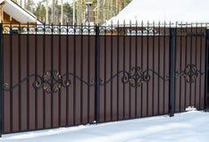 Smeedijzeromheining met een poort op de privésector in een buitenhuis in de wintersneeuw stock fotografie