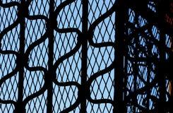 Smeedijzerpoort in backlight, blauwe hemel erachter Royalty-vrije Stock Foto's